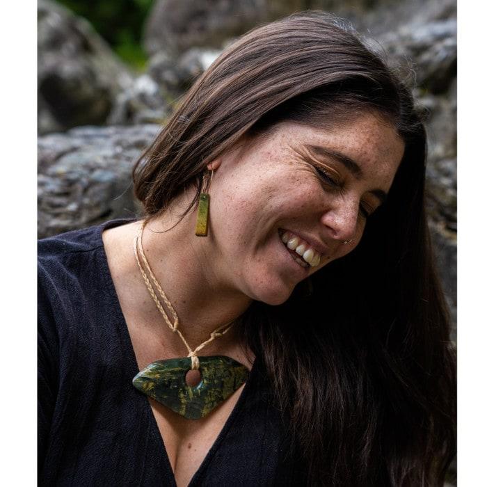 Marsden Flower Jade earrings and large korma pounamu breastplate pendant on model